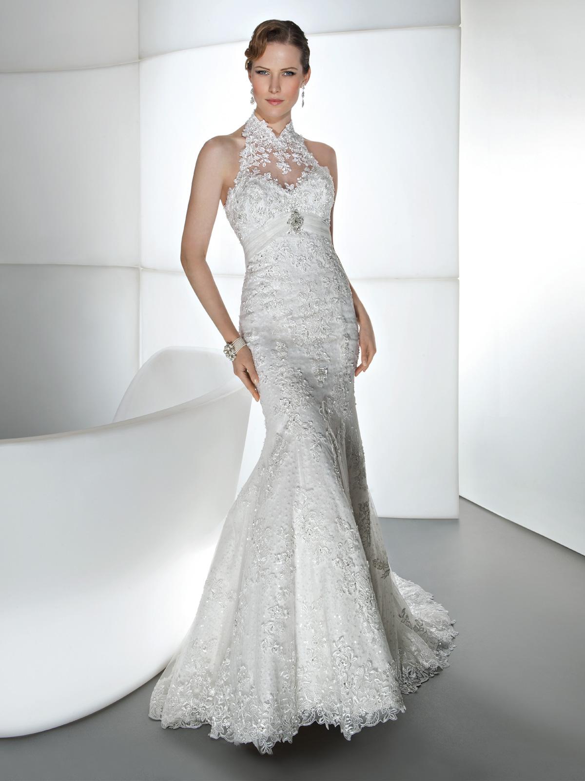 Vestido de Noiva cava americana, em renda rebordada, corte sereia e broche de metal no decote, leve cauda.