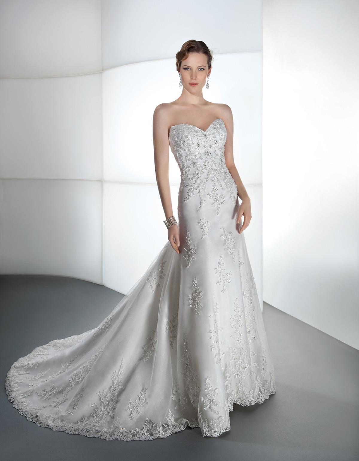 Vestido de Noiva tomara que caia, em renda levemente rebordada em pedrarias, decote princesa e suave cauda.