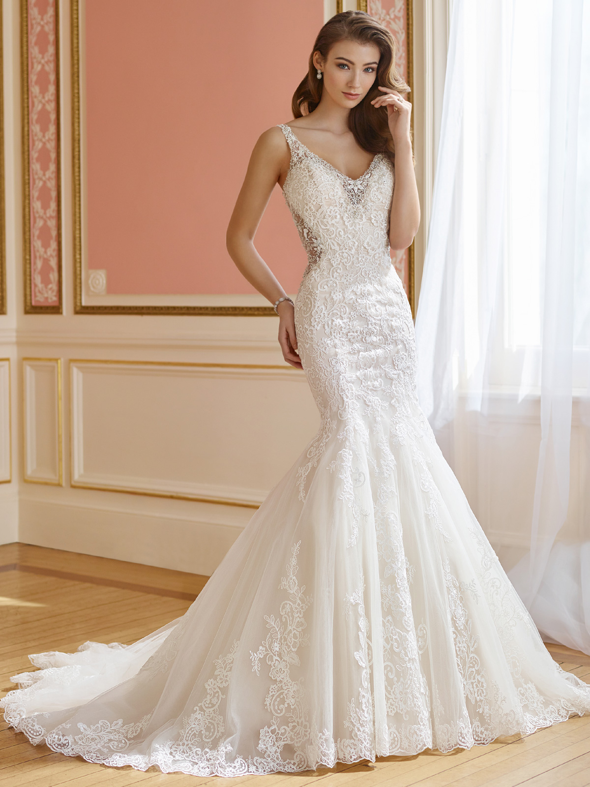 Vestido de Noiva charmosa com decote V e costas e lateral do corpo na transparência, corte sereia todo confeccionado em renda rebordada com cristais, cauda média.