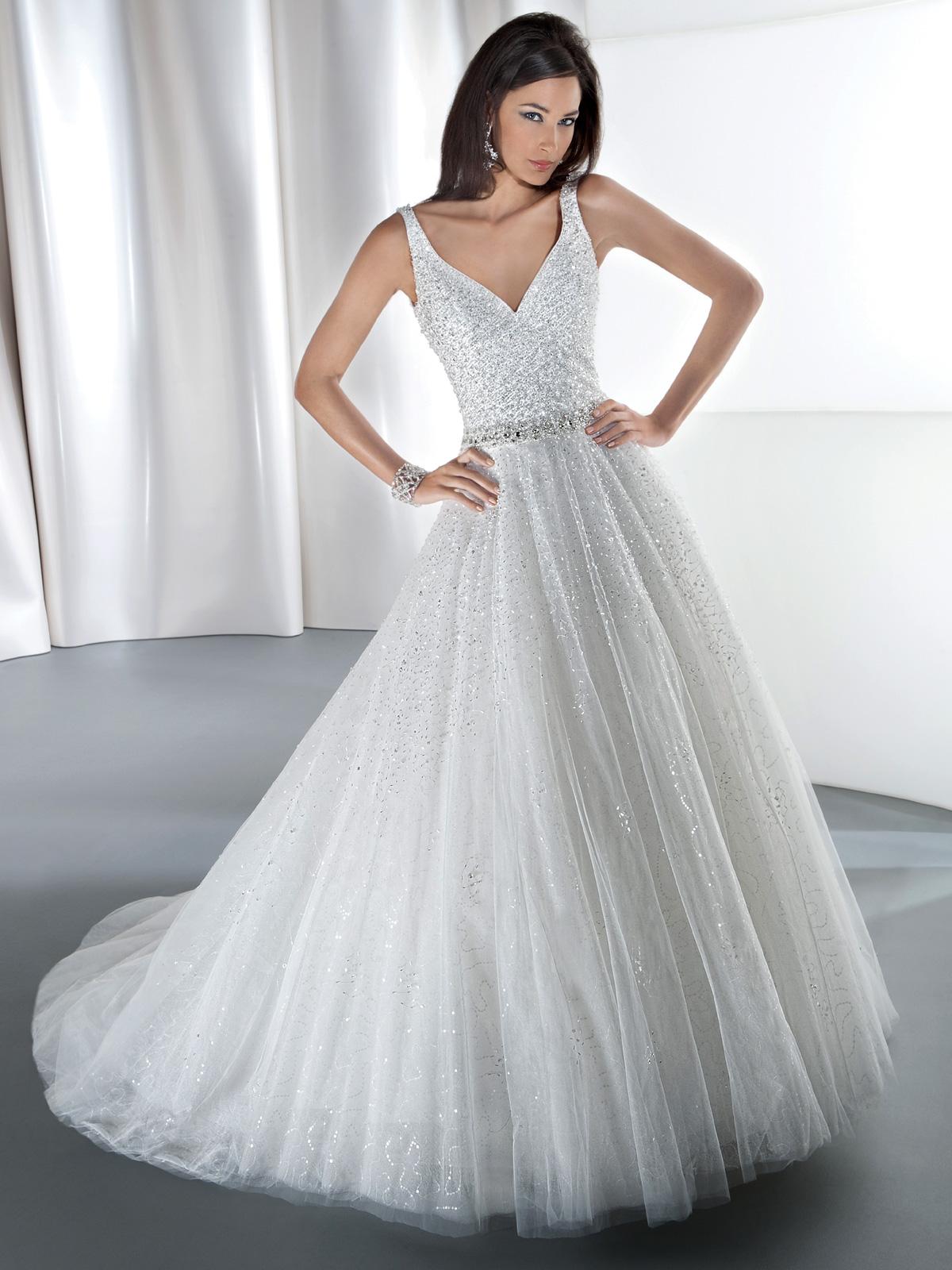 Vestido de Noiva com decote V frente e costas, corpo e saia rebordados em pedraria, confeccionado em tule, leve cauda.