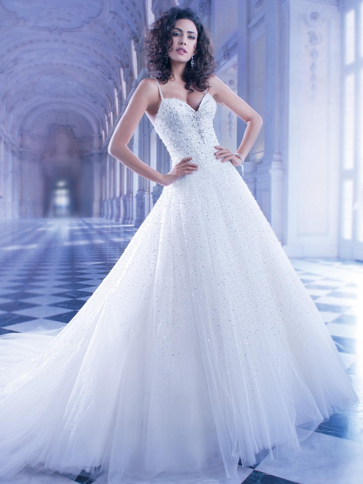 Vestido de Noiva em tule decote princesa e alças finas, com bordado estilo cascata com pedrarias e cristais, mais concentrado no corpo e suavizando na saia, corselet eleve cauda.