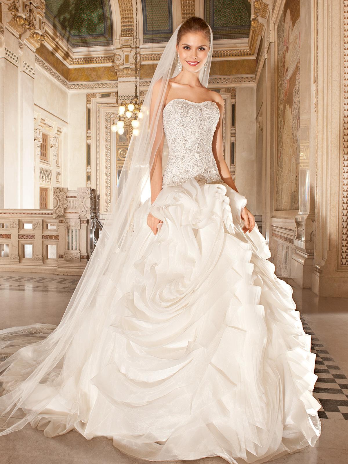 Vestido de Noiva Glamuroso, tomara que caia, com corpo alongado todo bordado em pedrarias e cristais, saia com camadas de organza em forma de pergaminhos entrelaçados e cauda.